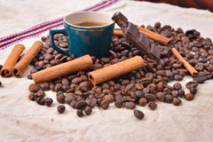 Cup of hot coffee with cinnamon sticks, bitten bar of chocolate Stock Photos