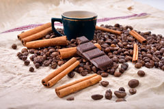 Cup of hot coffee with cinnamon sticks, bitten bar of chocolate Stock Images