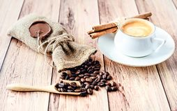 Cup of hot coffee, cinnamon sticks and coffee beans in a wooden scoop and spilling out from a hessian bag on wooden. Rustic table. Close-up royalty free stock photo