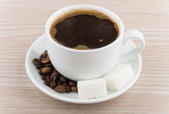 Cup of hot coffee, coffee beans and pieces of sugar Stock Photography