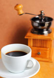Cup of hot coffee with coffee grinder Stock Photography