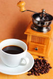 Cup of hot coffee with coffee grinder Royalty Free Stock Photography