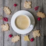 Cup of hot coffee, cookies in form leaves, dry autumn leaves, hawthorn and barberry fruits on a wooden background. Top view, flat royalty free stock images