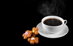 A cup of hot coffee and cookies isolated on a black background. Royalty Free Stock Image