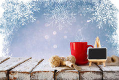 Cup of hot coffee and cozy knitted scarf and blackboard on wooden table Stock Photo