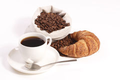 Cup of hot coffee with croissants and beans Royalty Free Stock Images