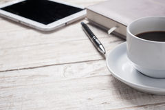 Cup of hot coffee and diary on wood table Royalty Free Stock Photography