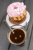 Cup of hot coffee with donuts on black Royalty Free Stock Photo