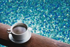 Cup of hot coffee drinks on wood table, with water in swimming pool background Stock Photography