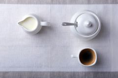 Cup of hot coffee espresso, coffee beans, jug of milk, and bowl with sugar on white background for copy space. Coffee Royalty Free Stock Photography
