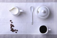 Cup of hot coffee espresso, coffee beans, jug of milk, and bowl with sugar on white background for copy space. Coffee Stock Images