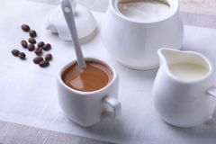 Cup of hot coffee espresso, coffee beans, jug of milk, and bowl with sugar on white background for copy space. Coffee Stock Photo