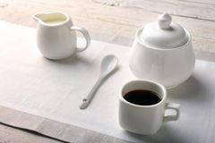 Cup of hot coffee espresso, coffee beans, jug of milk, and bowl with sugar on white background for copy space. Coffee Stock Image