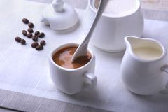 Cup of hot coffee espresso, coffee beans, jug of milk, and bowl with sugar on white background for copy space. Coffee Royalty Free Stock Image