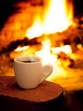 A cup of hot coffee in fron of fireplace Royalty Free Stock Photography