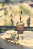 Cup of hot coffee and glass of blend coffee in retro filter effe Royalty Free Stock Image