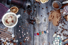 Cup of hot coffee on a gray wooden surface. Sweets and a book, top view Stock Photography