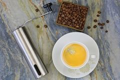 Cup of hot coffee with hand coffee grinder to grind beans. Top v. Iew of mini grinding made of steel with handle to make freshly ground coffee drink on stone Stock Images