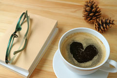 Cup of hot coffee with heart shape foam on wooden table with some books, glasses and pine cones. Background Royalty Free Stock Images