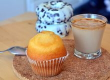 Cup of hot coffee and homemade sweet muffins and donuts. Stock Photos