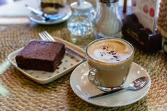 A cup of hot coffee late with brownie cake in coffee shop.  royalty free stock photo