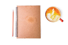 Cup of hot coffee latte art  with open note book and pencil Stock Photo