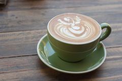 Cup of hot coffee latte with beautiful style on wood table Royalty Free Stock Images