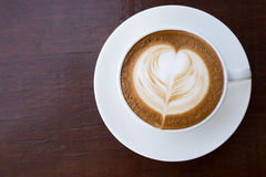 Cup of hot coffee latte with heart shaped foam art Stock Photos
