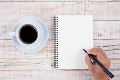 Cup of hot coffee and man hand writing notebook  on white wood t Stock Photography