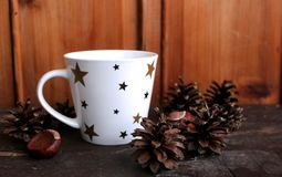Cup of hot coffee with milk on wood background, cone and chestnuts as decoration.Retro style. Sunday relax and still life concept. Free place for text,blurred Royalty Free Stock Image