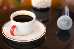 Cup of hot coffee in music  on black  background. Cup of hot coffee mic in music  on black  background Royalty Free Stock Photo