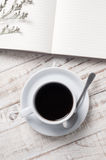 Cup of hot coffee and  note book on wood table background Royalty Free Stock Photo