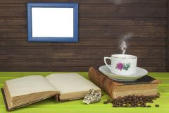 Cup of hot coffee and old book. Relaxing at the coffee. Studying old books. Place for your text. Stock Photo