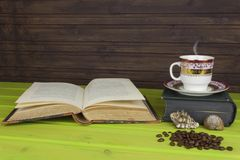 Cup of hot coffee and old book. Relaxing at the coffee. Studying old books. Place for your text. Royalty Free Stock Photo