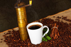 Cup of hot coffee with Old-fashioned coffee grinder Stock Image