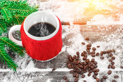 Cup of hot coffee on the old snowy table and christmas tree branch in sunshine, coffee beans. Stock Image