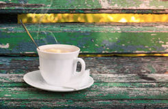 Cup of hot coffee is on old wooden bench Royalty Free Stock Image