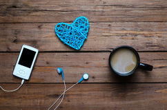 A cup of hot coffee and a player with headphones on a wooden tab. Le, top view. Morning coffee and favorite music Royalty Free Stock Images