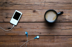 A cup of hot coffee and a player with headphones on a wooden tab. Le, top view. Morning coffee and favorite music Royalty Free Stock Image