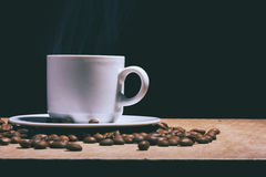 Cup of hot coffee and saucer on a brown table. Dark background. Royalty Free Stock Photo