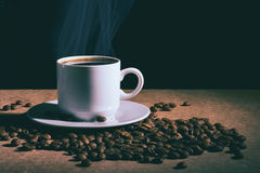 Cup of hot coffee and saucer on a brown table. Dark background. Stock Photography