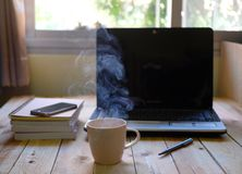A cup of hot coffee smoke and a book, computer on wood table stock image