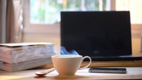 A cup of hot coffee smoke and a book, computer on wood table stock photo