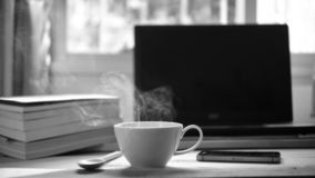 A cup of hot coffee smoke and a book, computer on wood table royalty free stock photography