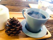 Cup of hot coffee. With smoke and pine nut on wood desk Royalty Free Stock Images