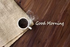 Cup of hot coffee with smoke on wooden table top view Royalty Free Stock Photography