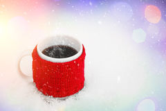Cup of hot coffee on the snow. Feeling of comfort and holiday mood. Xmas and New Year fairy tale background. Stock Photography