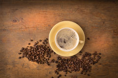 Cup of hot coffee and some beans. Cup of coffee, hot with some beans on a wooden surface Stock Photo
