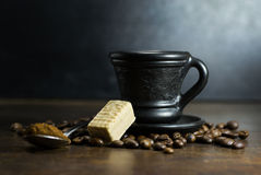 Cup of hot coffee with spoon and candy. On wooden background stock photo