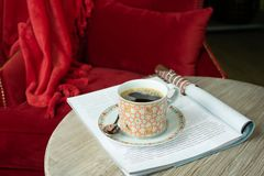 A cup of hot coffee stands on the table against the backdrop of a red chair and a soft plaid. Food concept. Copy space. royalty free stock photography